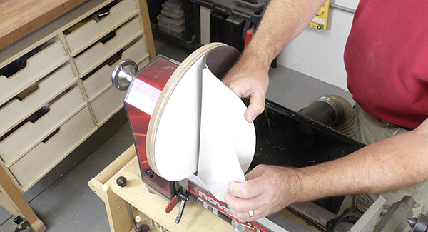 A man applies an adhesive-baked sanding disc to the platen