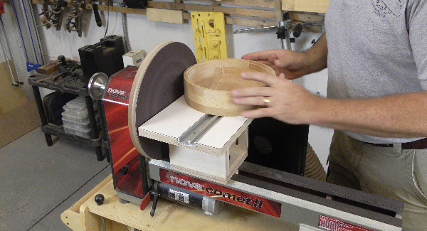 A craftsman uses a lathe sanding disc to sand a round object