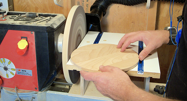 A craftsperson sands a circle of wood using a lathe