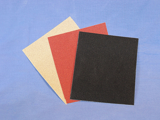Three sheets of sandpaper displaying different abrasive materials