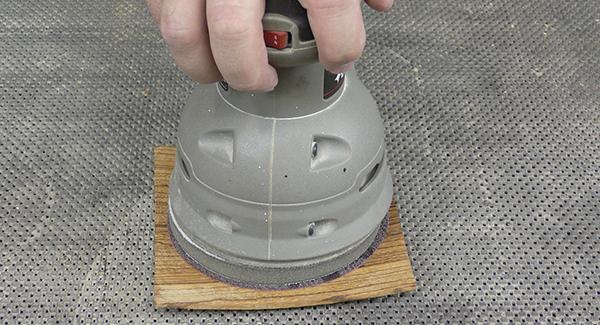 A random orbit sander being used to create soft curves on wood